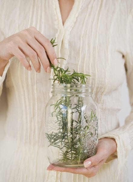 Woman taking herbs out of jar