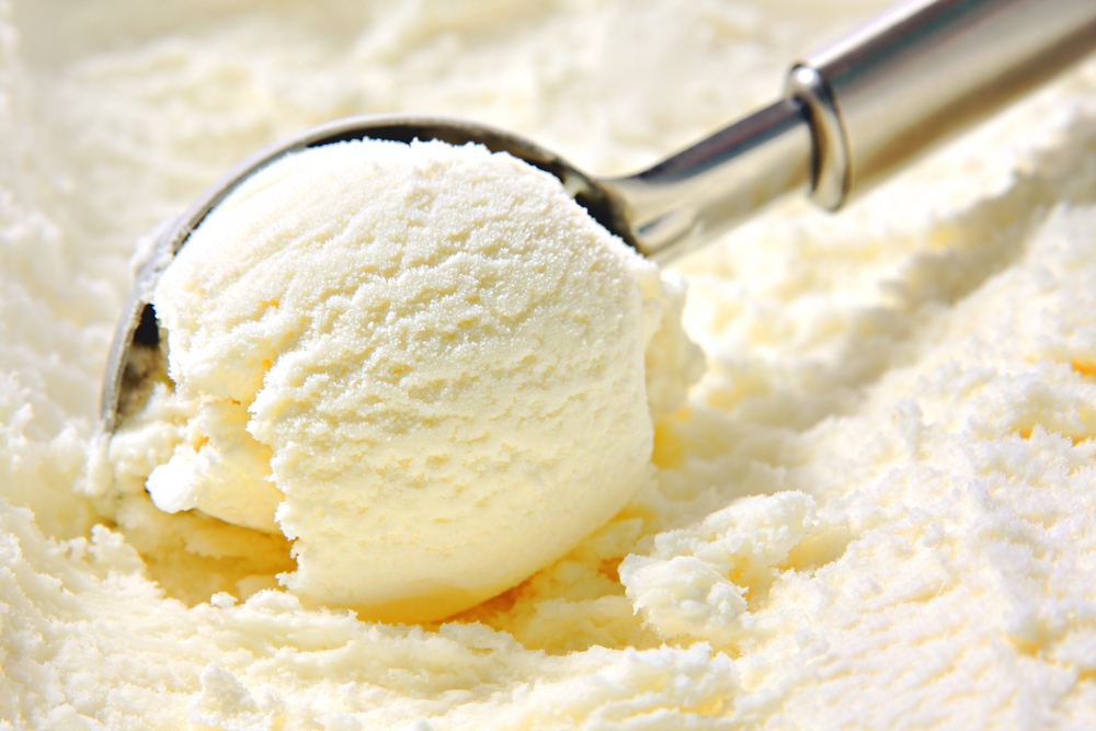 Vanilla ice cream being scooped out of a container.