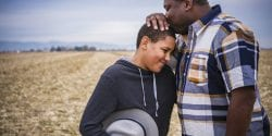 Father kissing son on head in field