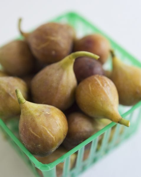 Figs sitting in a green produce basket