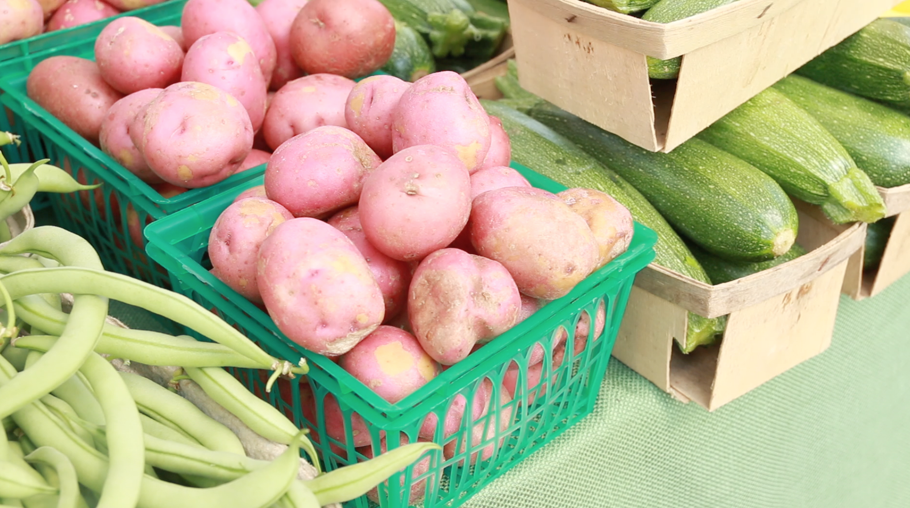 Potatoes, green beens and zucchini squash at a farmers market.