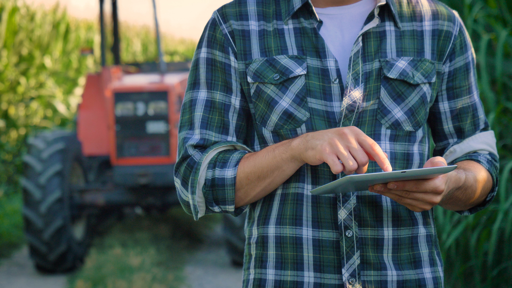 Farmer on a tablet with tractor in background