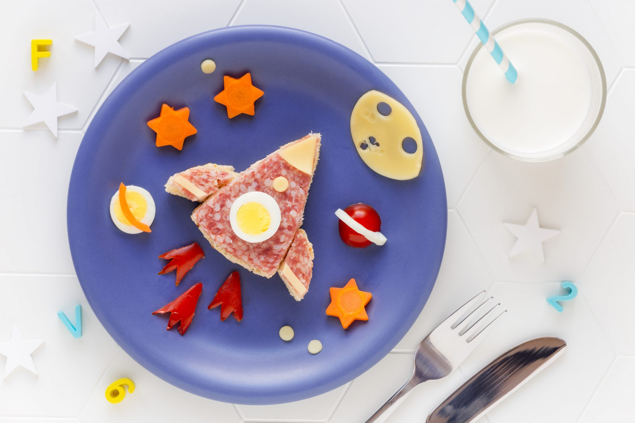 rocket or space shuttle shaped sandwich with cheese and salami decorated with stars, moon and planets on a blue plate