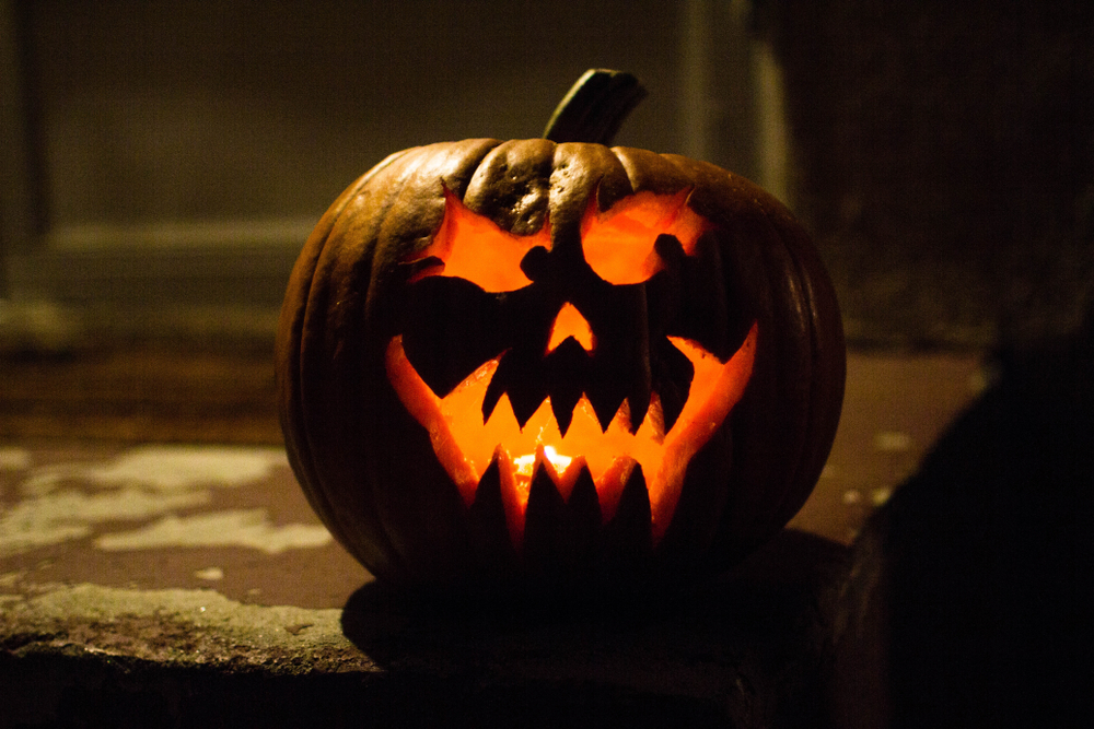 A jack o lantern sitting on a porch.