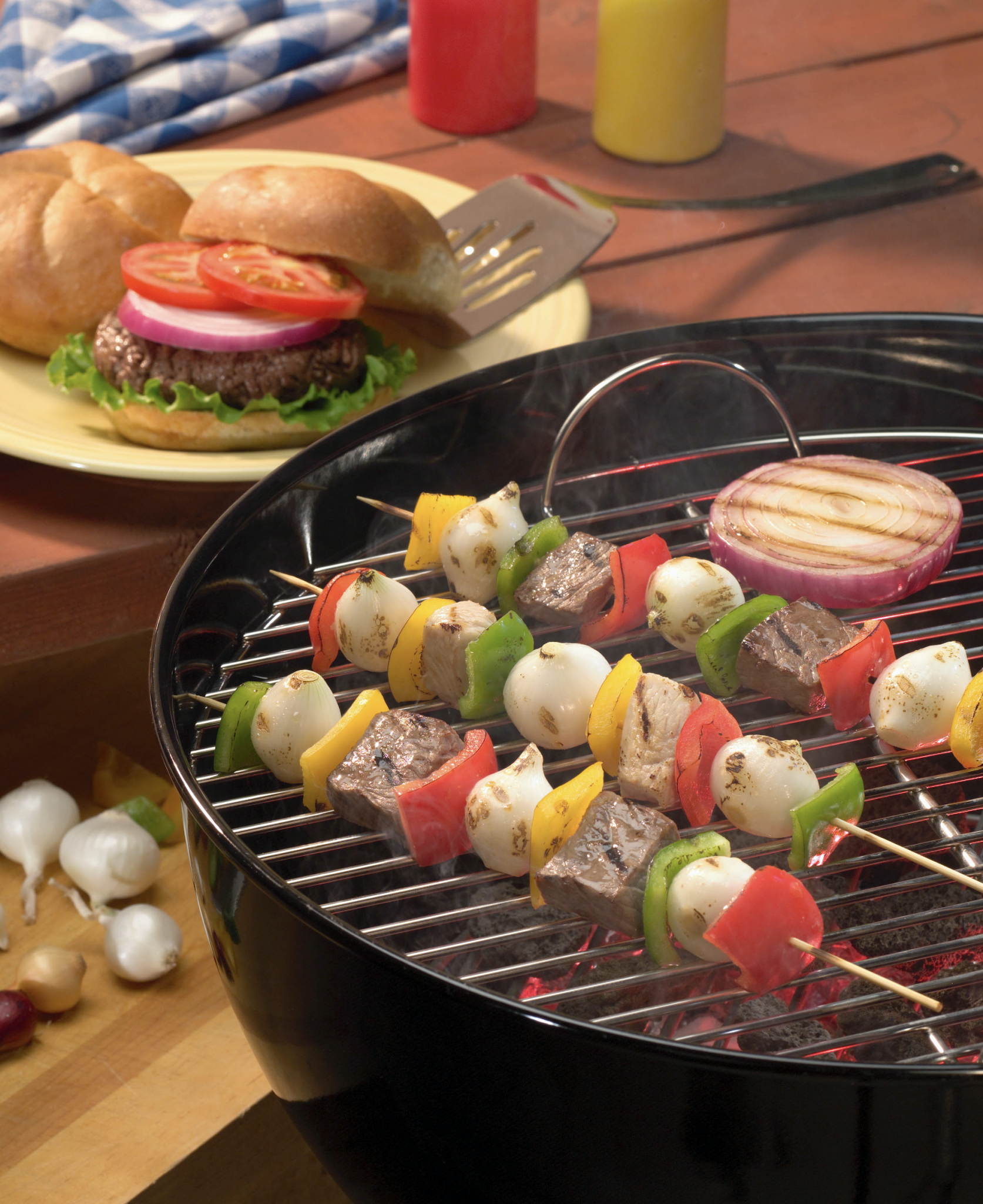 vegetable on skewers on a grill, hambuger on a plate on a picnic table