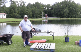 A man standing near a pond building a floating living fish attractor.