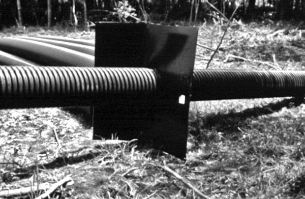 Figure 7. While we recommend smooth steel, PVC, or aluminum for the barrel through the dam and not the corrugated pipe shown here, this picture does show the anti-seep collar designed to reduce leakage around the pipe.
