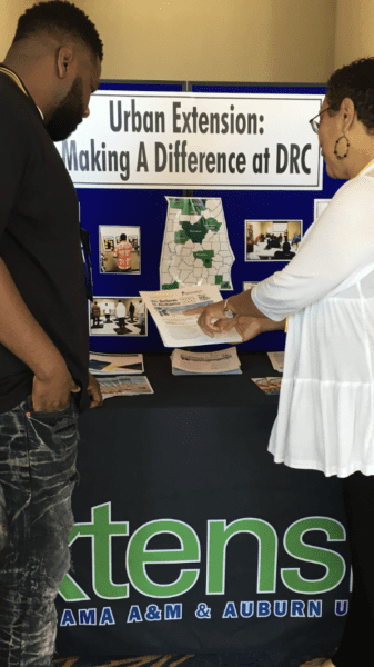Two people looking over Extension information booth at DRC Birmingham
