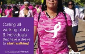 African American woman wearing pink smiles as she walks with a group in a breast cancer awareness walk.