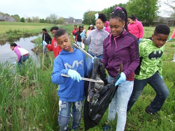 Students gather samples and clean up trash from urban stream