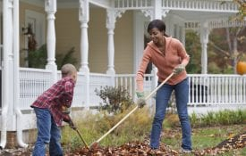 Mother and son raking leaves for a fall garden refresh.