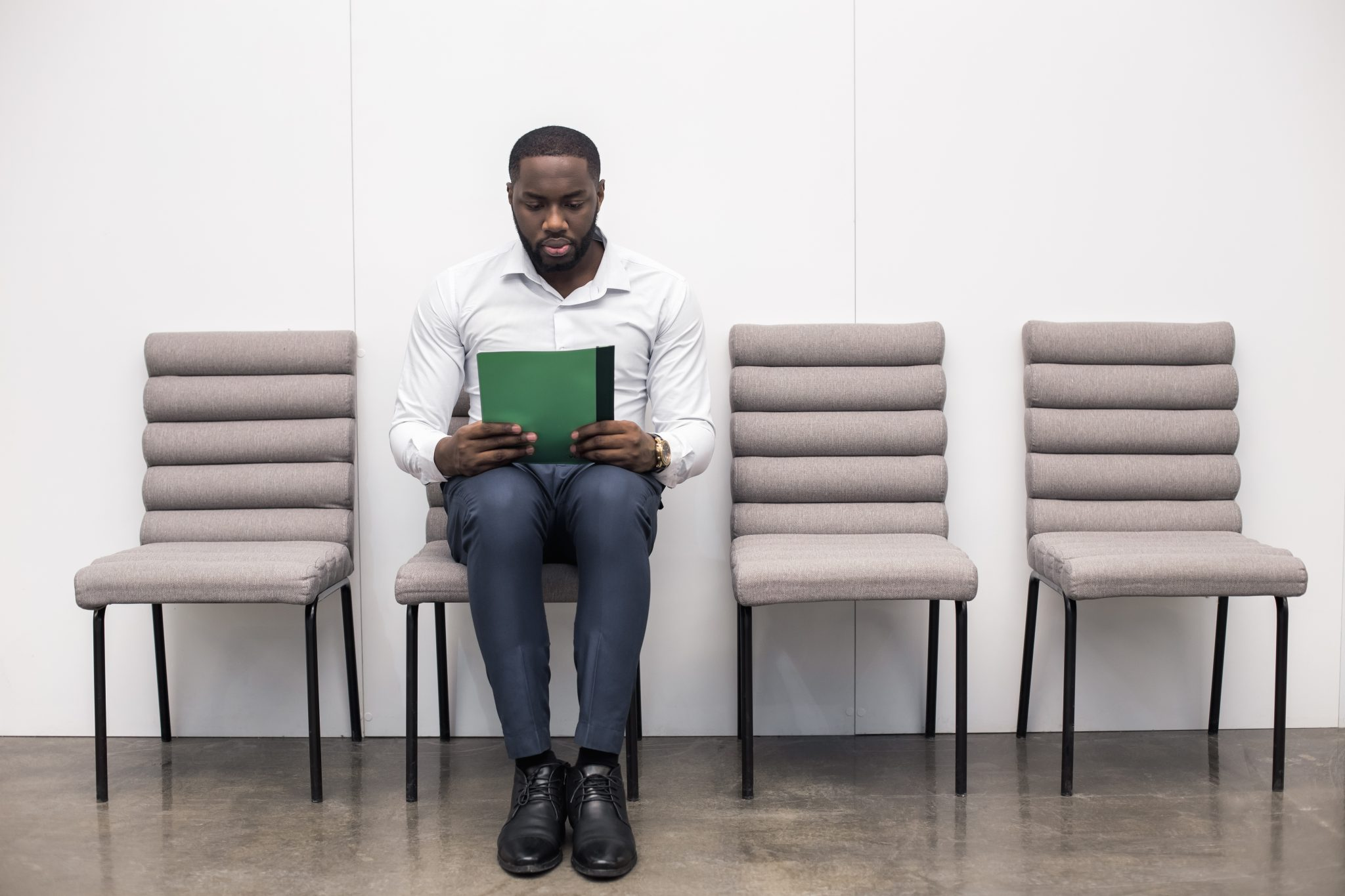 African American man in office. Man sitting, holding his CV and waiting for job interview.
