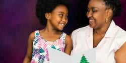 African mother reading a Christmas card to a little girl.