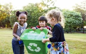 Children holding a recycling bin