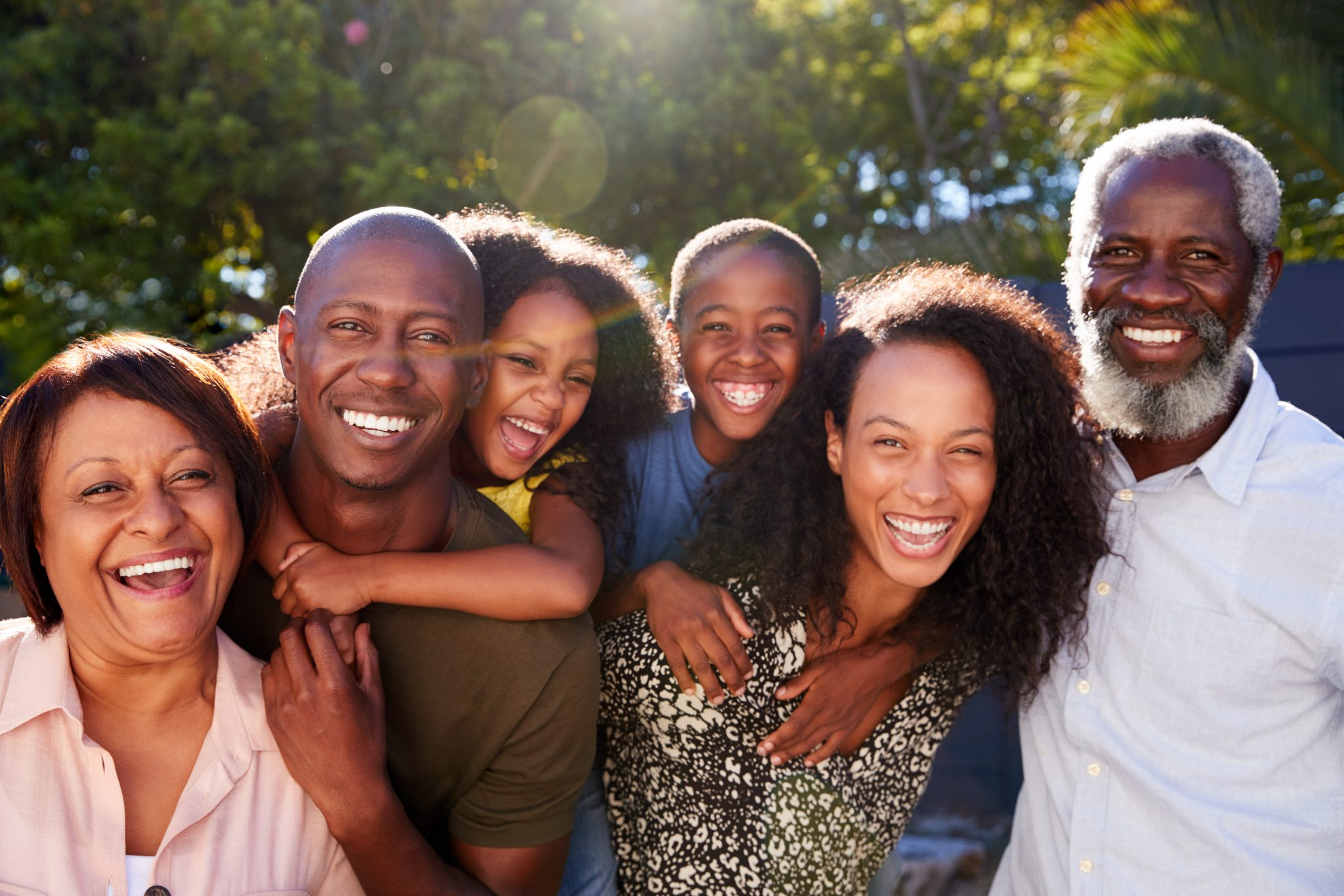 Outdoor Portrait Of Multi-Generation, African American Family In Garden At Home Against Flaring Sun