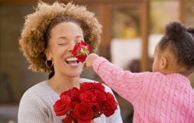 girl smelling roses with her mother