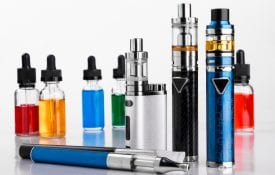 Modern electronic cigarettes and bottles with assorted vape liquid on white background