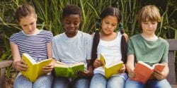 Children reading books at the park