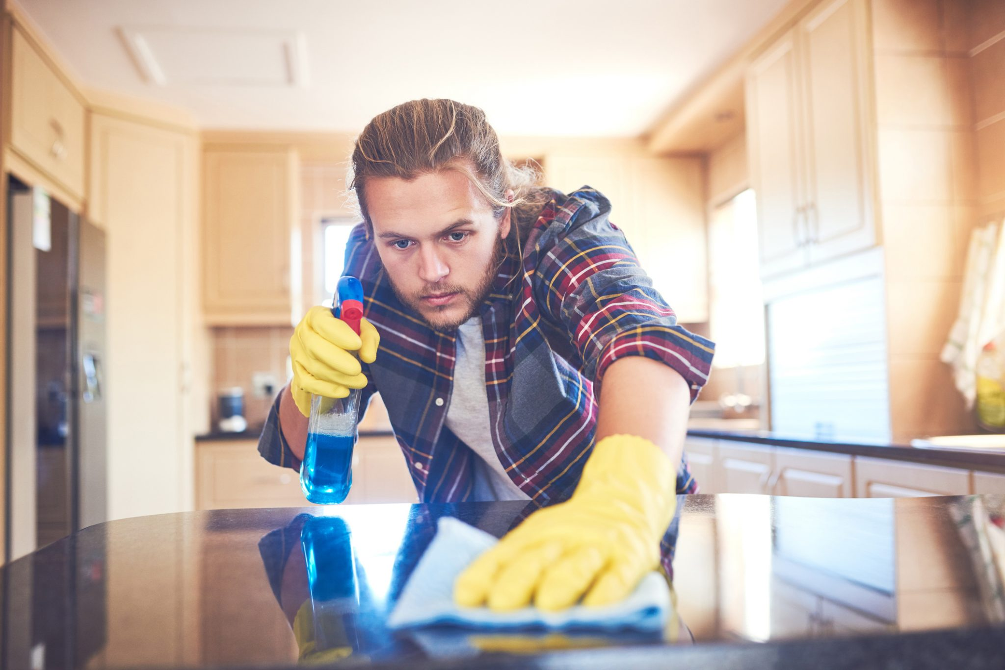 Shot of a young man sanitizing his kitchen