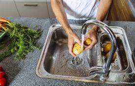 man washing vegetables in modern kitchen