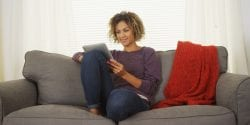 Young woman using a tablet on a couch.