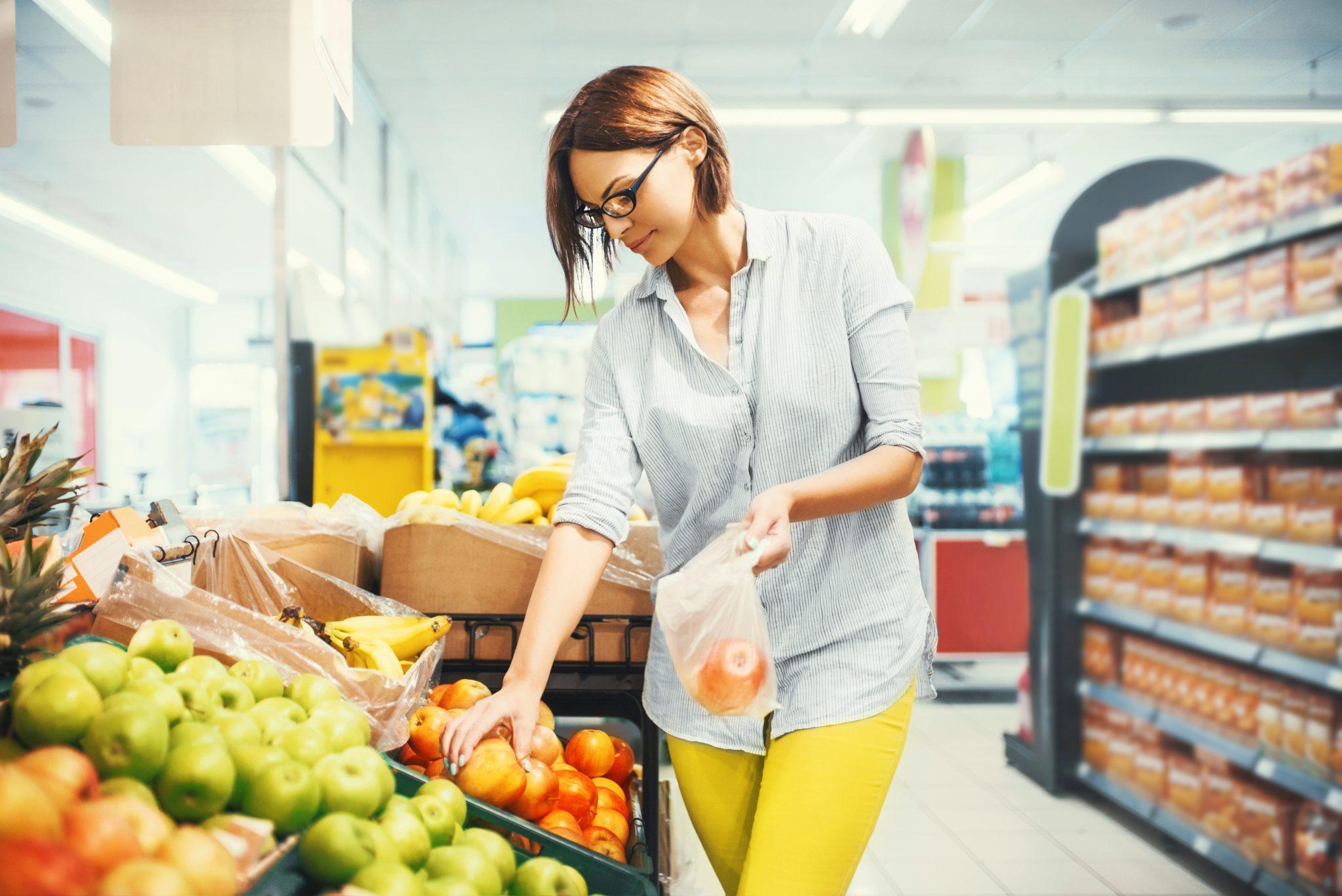 Woman choosing apples to buy in a supermarket.