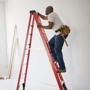 African American construction worker climbing ladder
