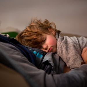 Toddler having a nap with dad in the sofa