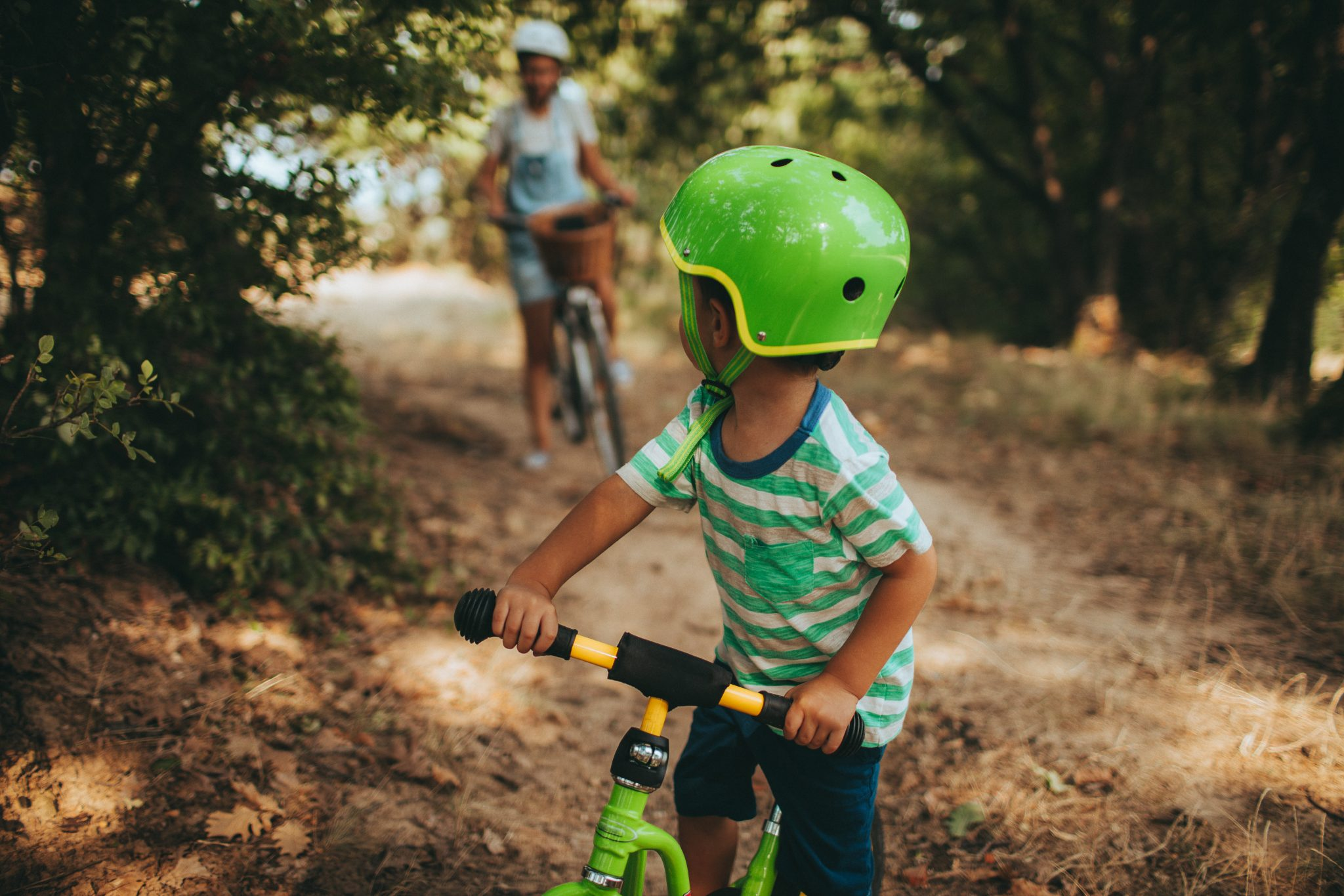 Little boy and his mother are riding bicycles outdoors in the nature