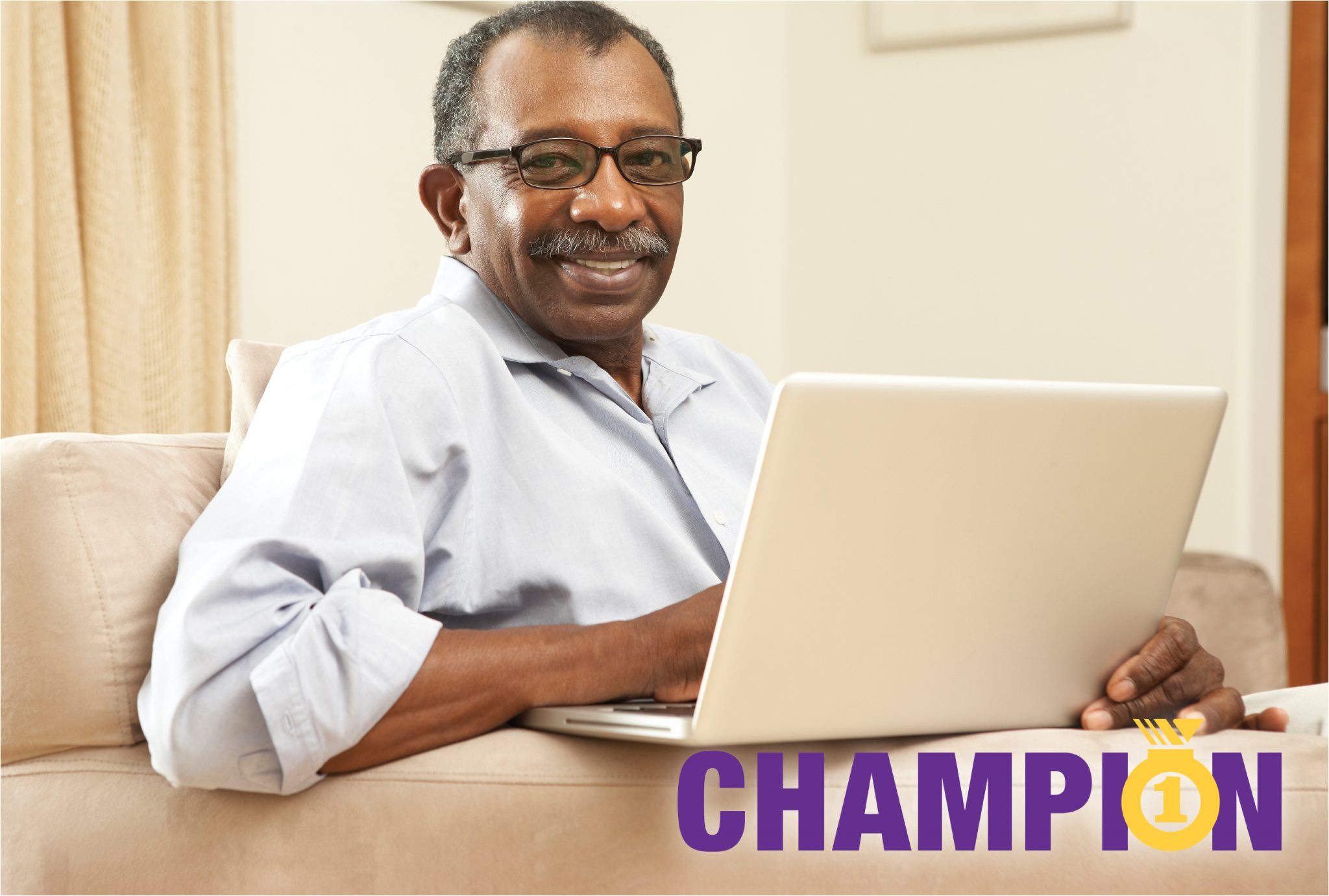 Older African AMerican man sits on his couch with his laptop computer