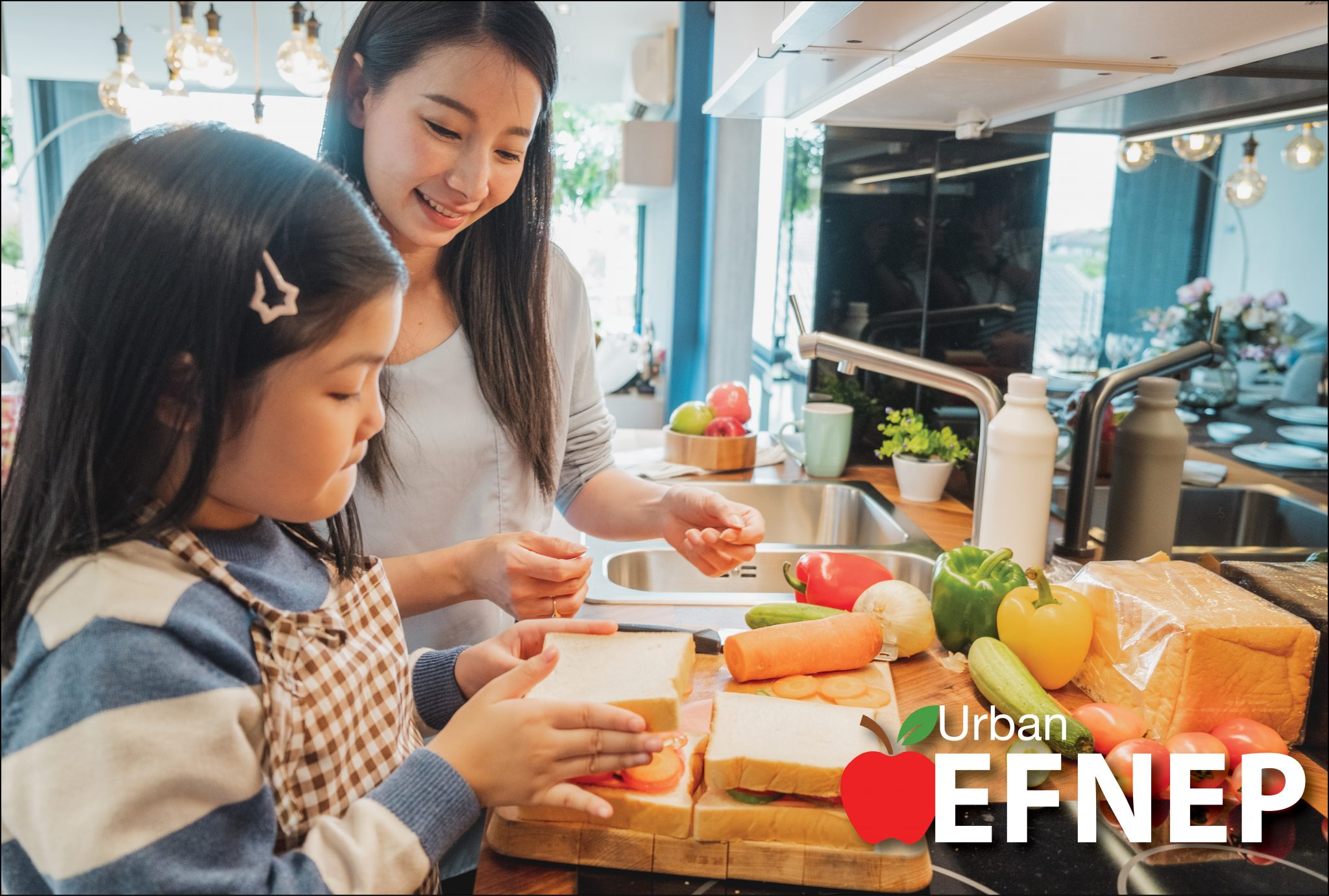 Asian mother and daughter make healthy vegetable sandwiches together in their kitchen