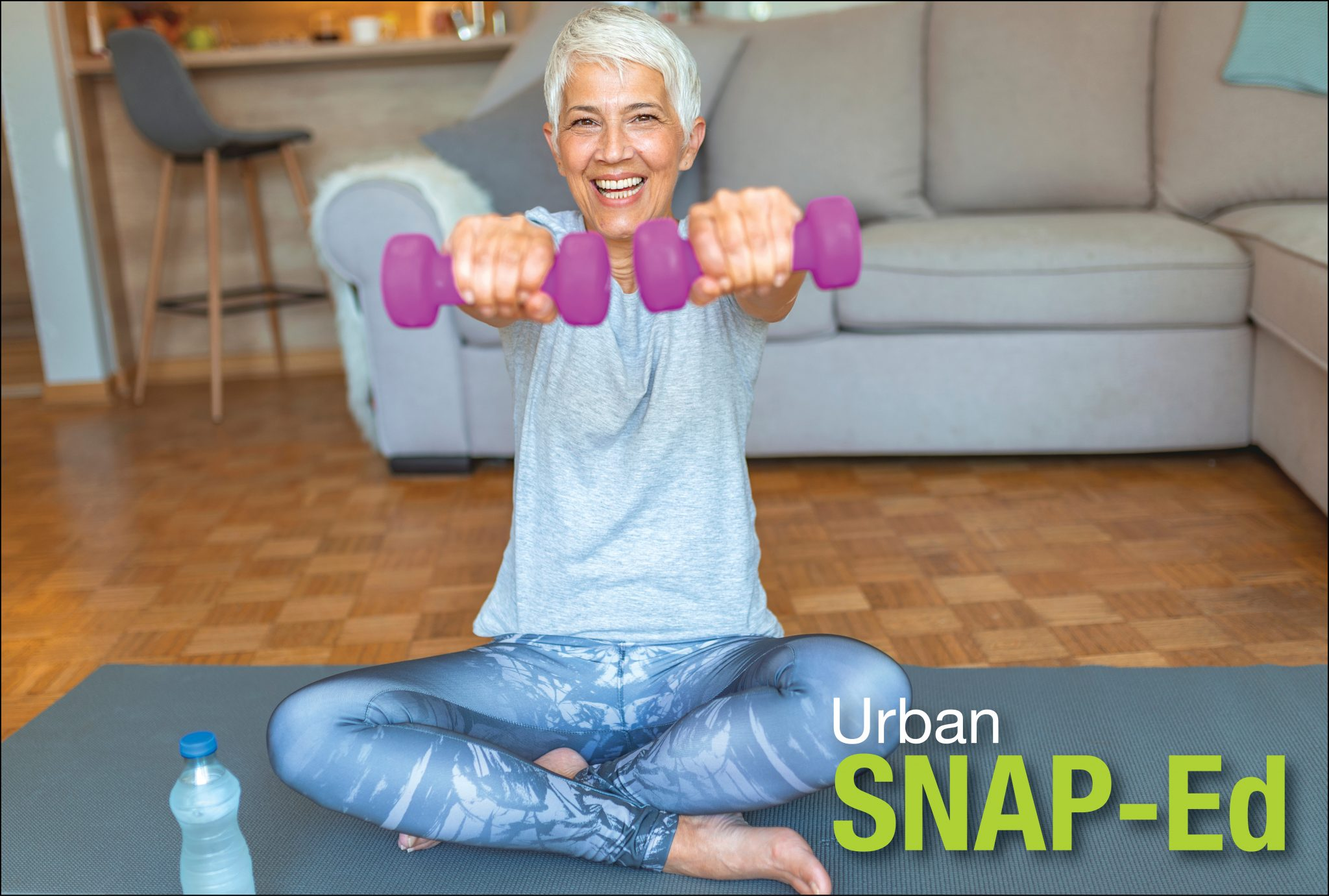 Older adult woman sitting on a yoga mat in her living room lifting hand weights. Drinking water.