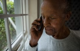 Serious senior man talking on mobile phone by window at home