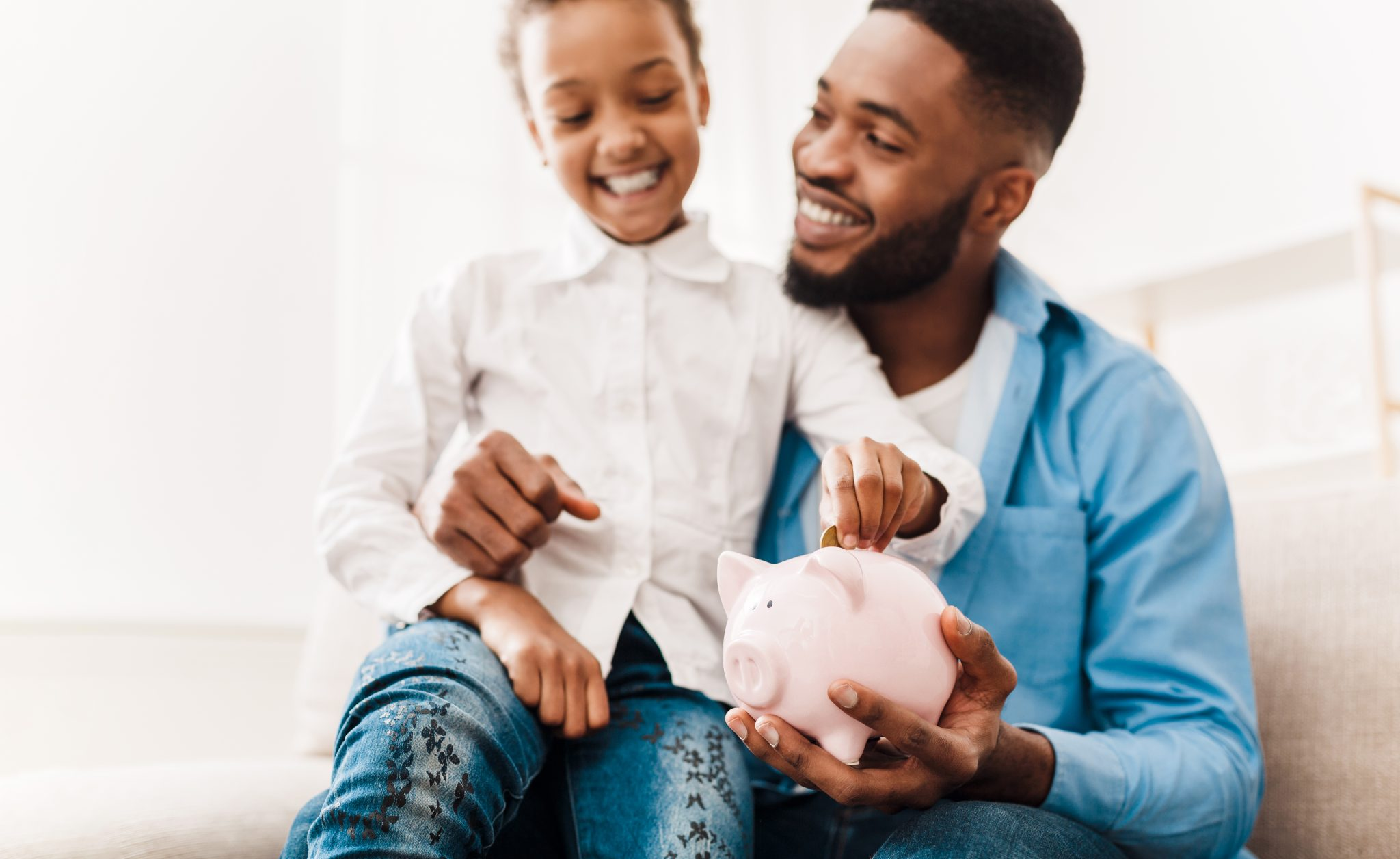 African American girl and father putting coin into piggy bank, sitting on sofa at home