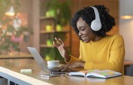 African American young woman in headset using laptop, having online conference