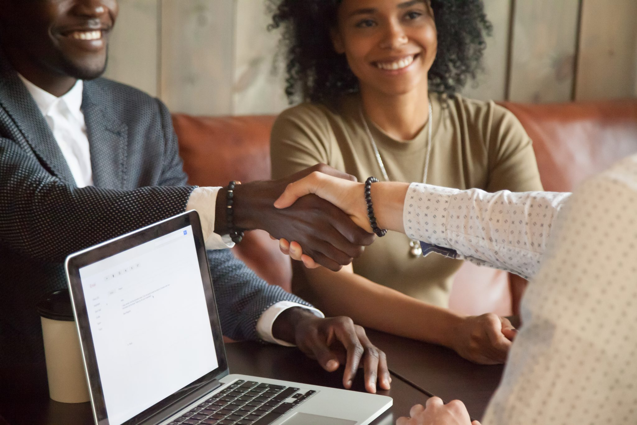 Happy african american couple making deal with loan agent, shaking hands