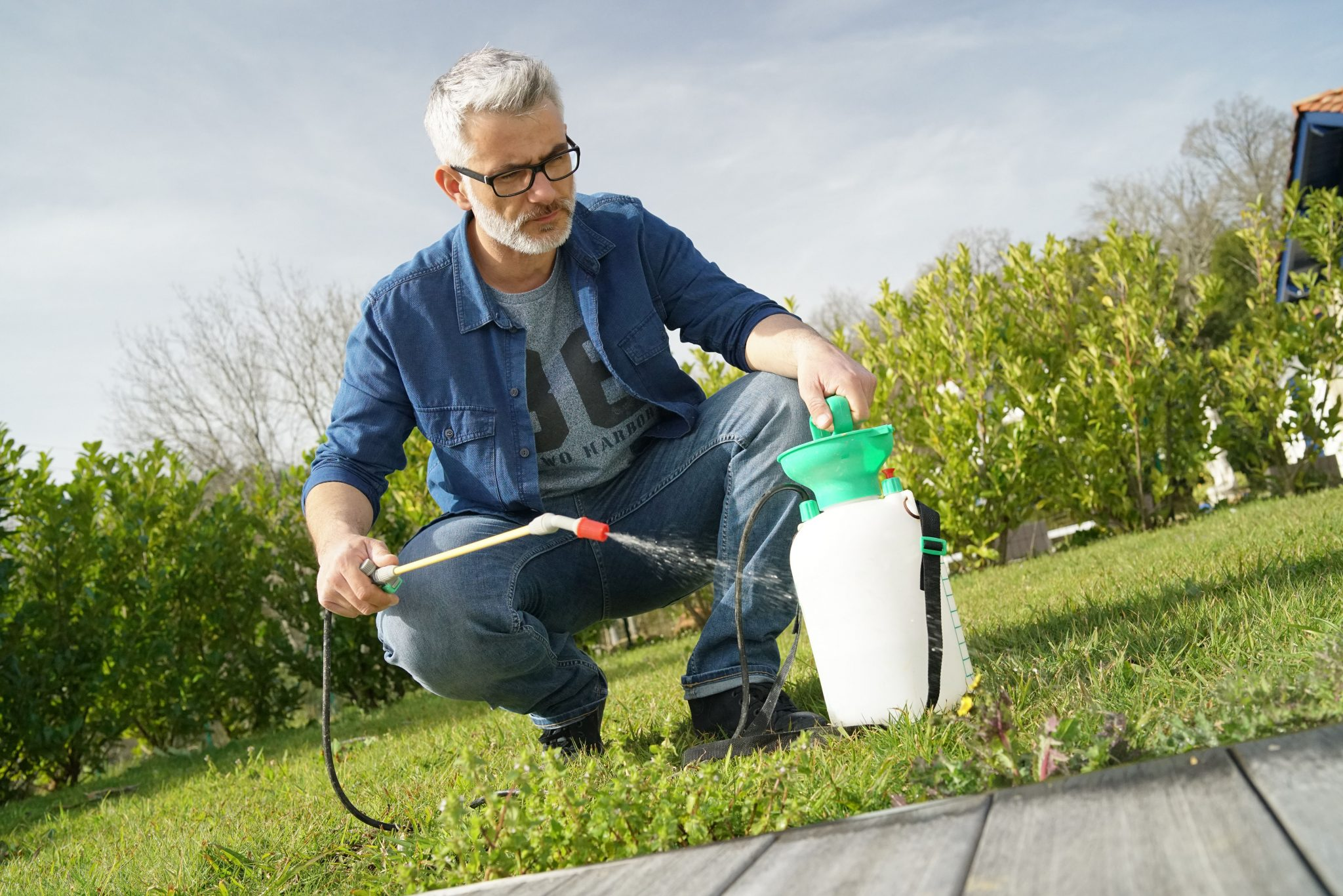 man using a sprayer in his yard.