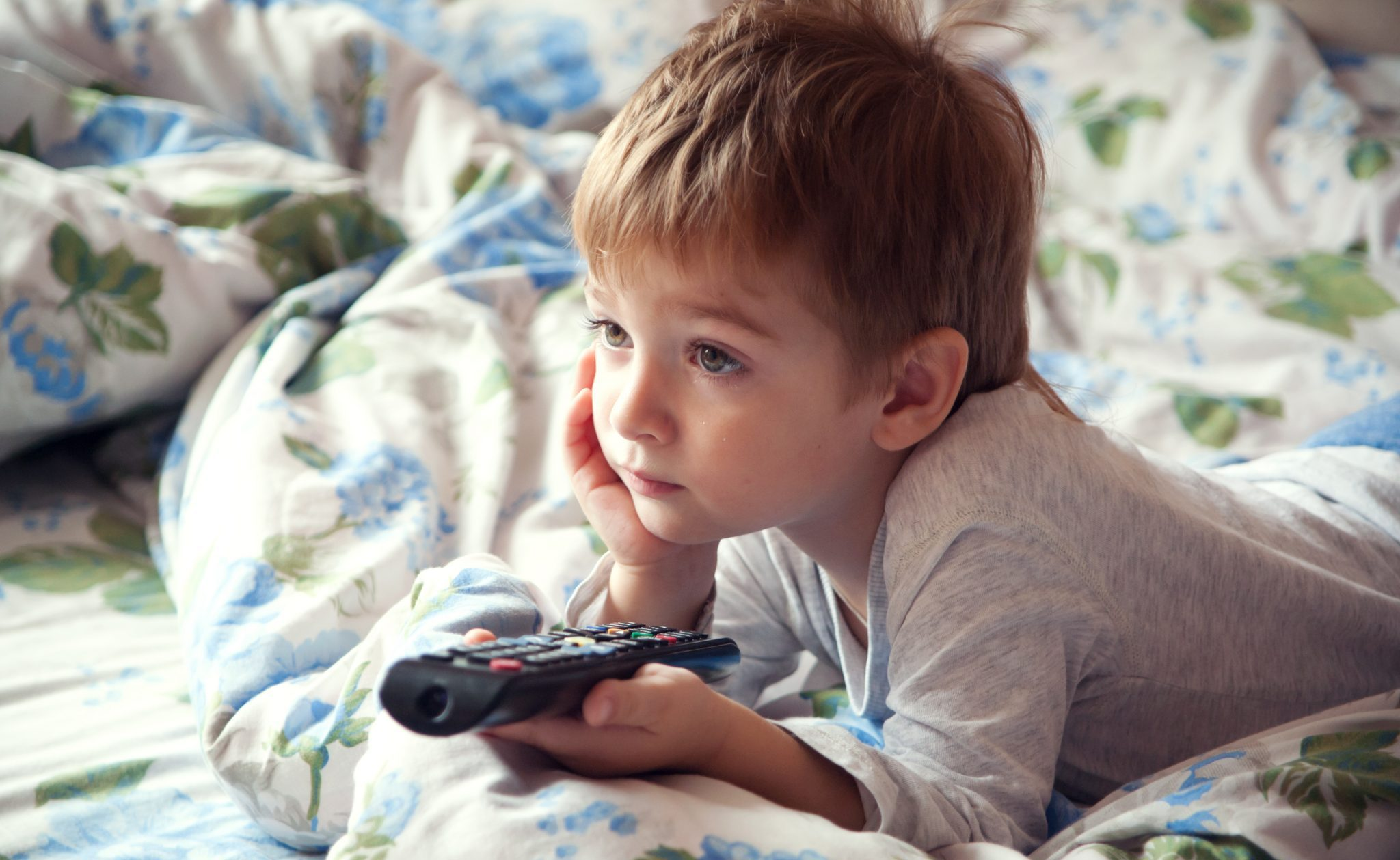 Young child laying on a bed watching TV.