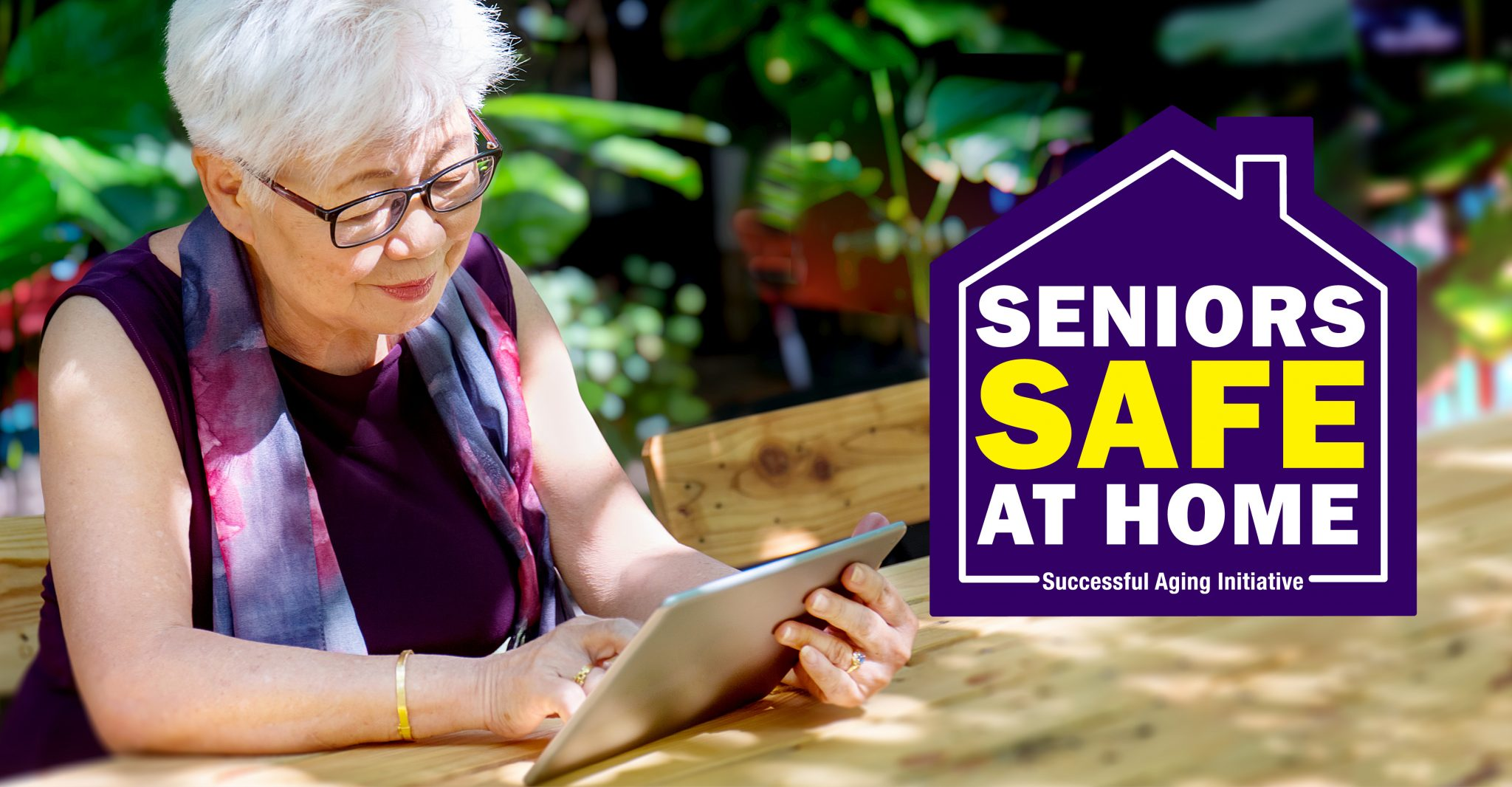 Asian American senior adult sits in her garden holding an ipad