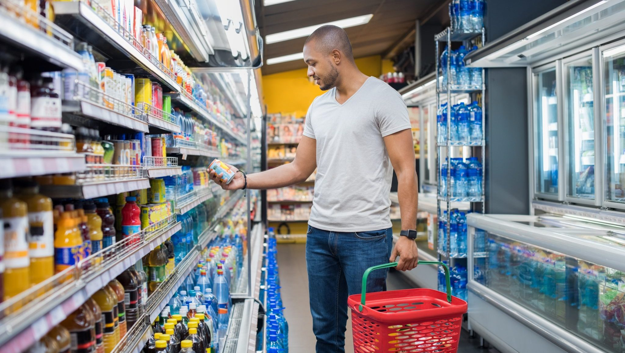 African American man at the grocery store reads a food label.