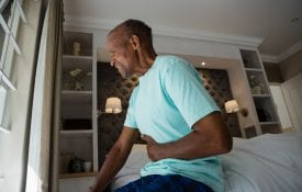Side view of senior man suffering from stomachache while sitting on bed at home