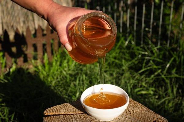 Pouring honey into a bowl