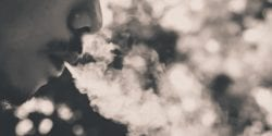 Man's face in a cloud of smoke.