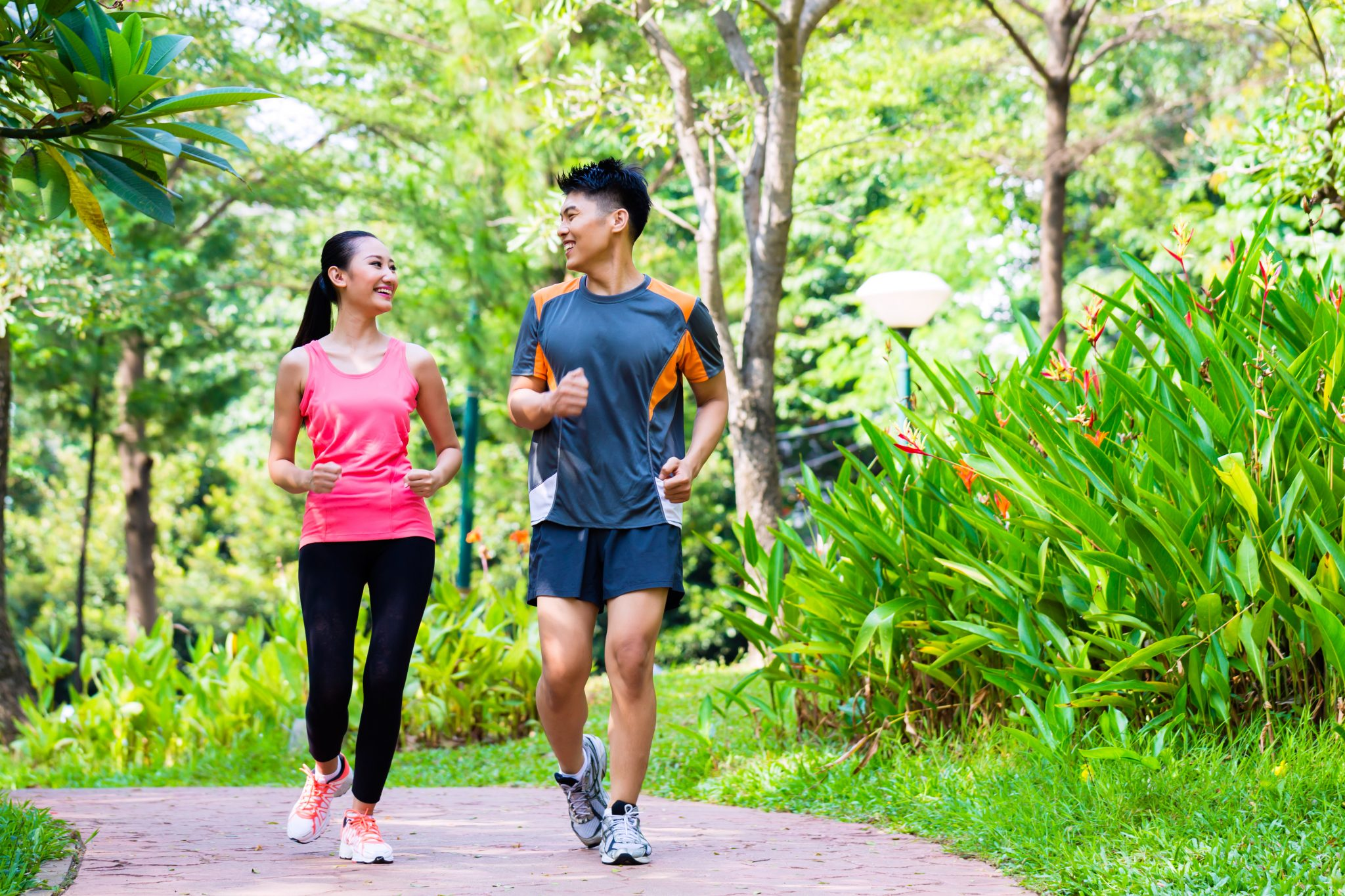 Young Asian couple jogging in a park.