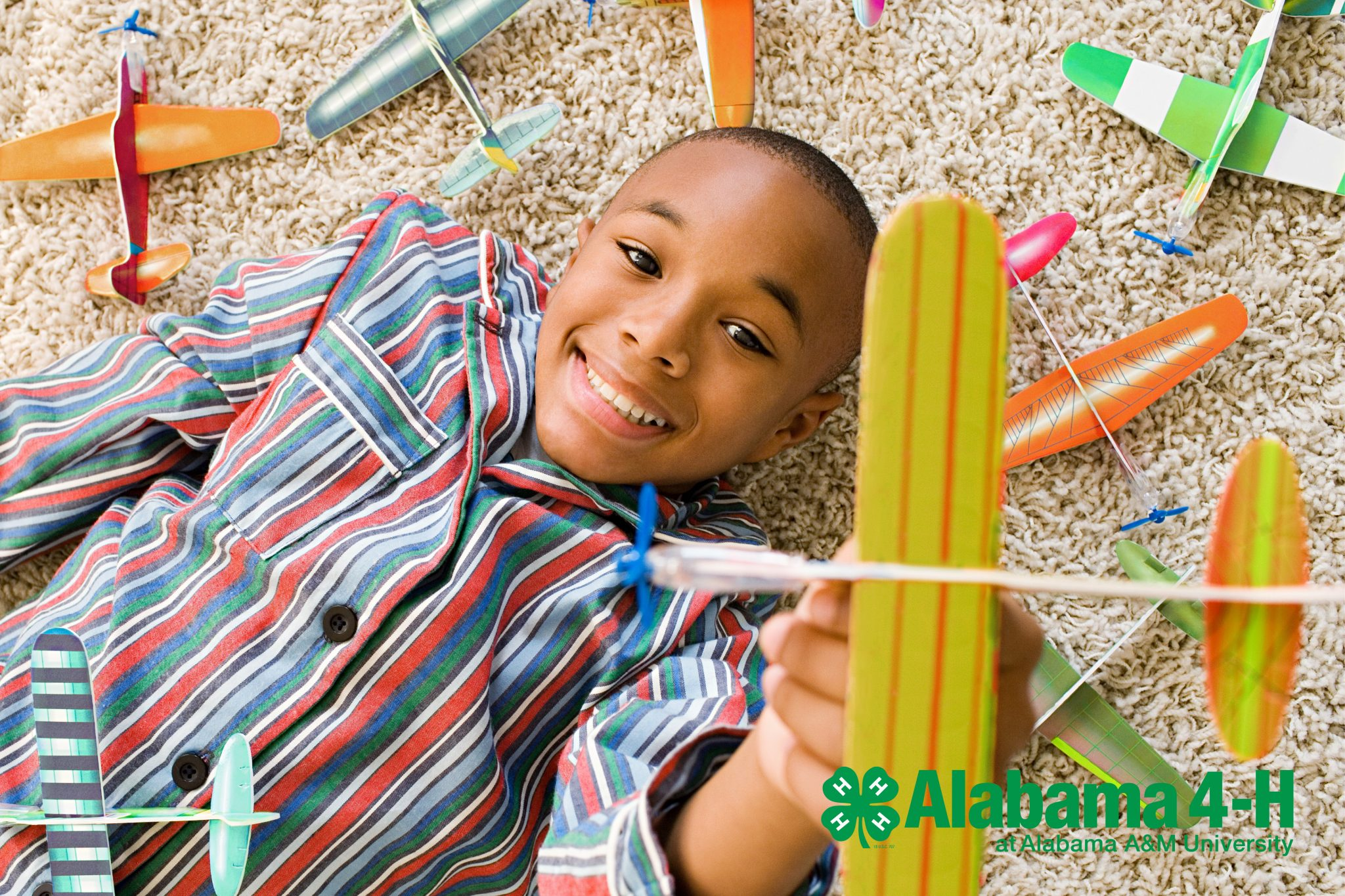 African American boy lays on the carpet playing with foam model airplanes