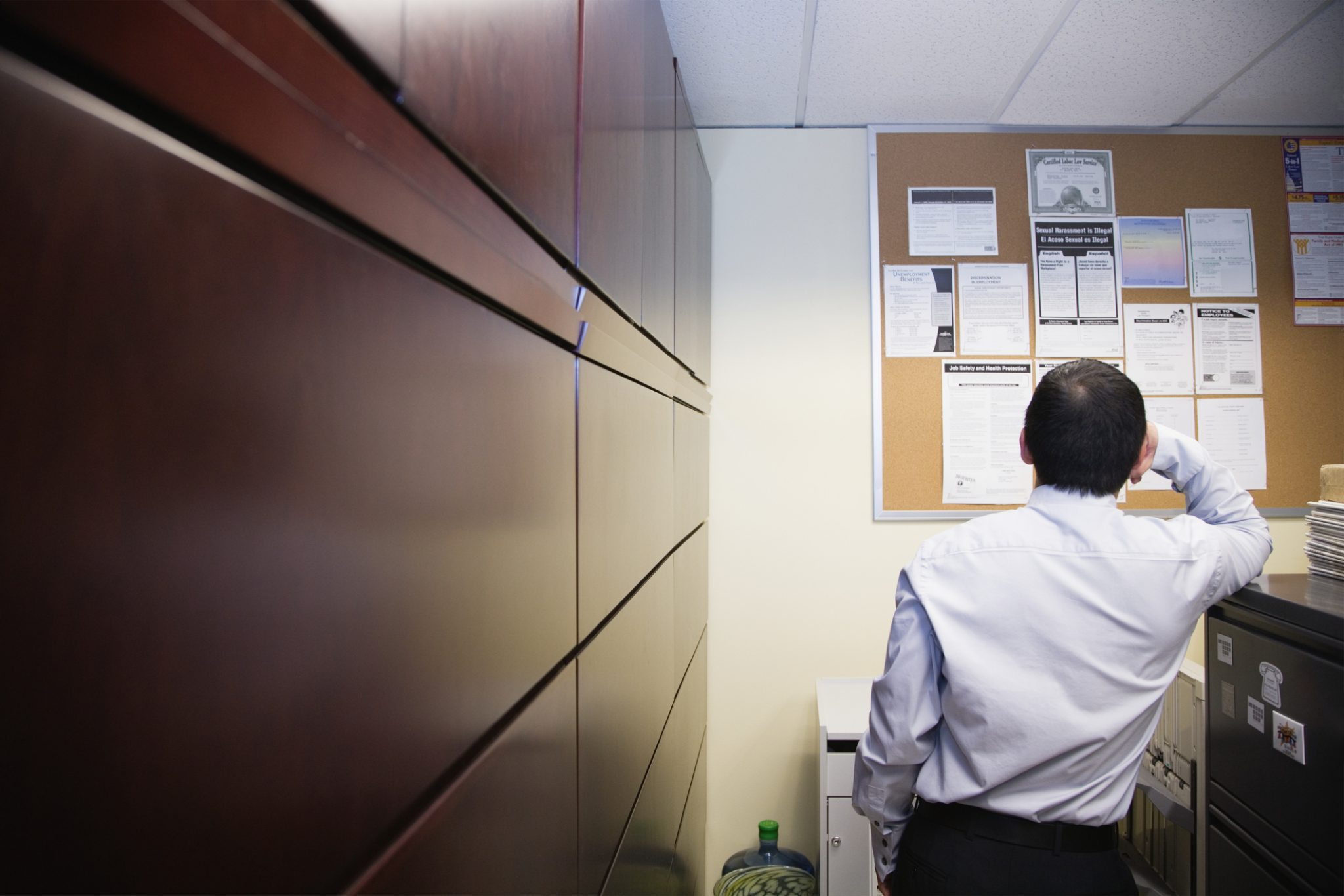 Businessman in a work place with posters on a cork board