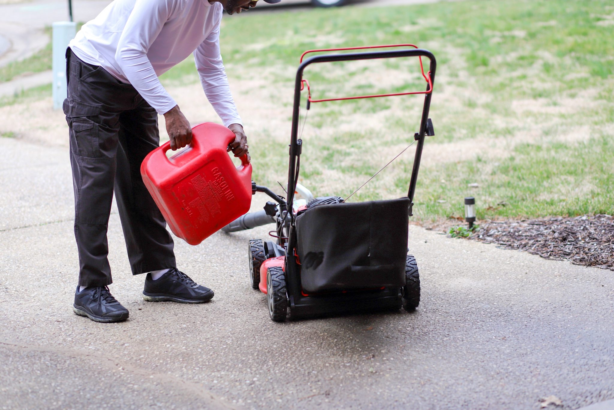 African-American man adding fuel to a lawnmower