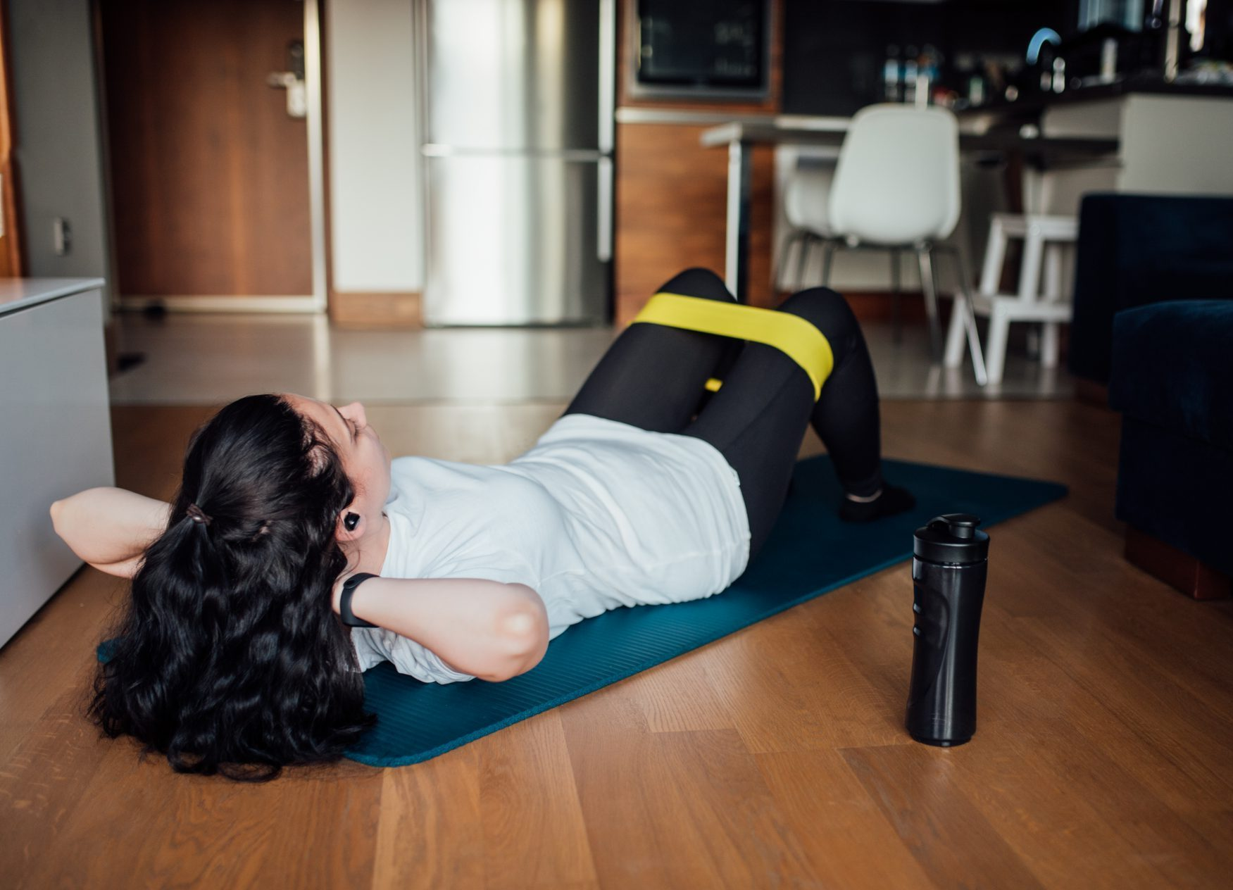 Woman doing exercises with resistance band at home