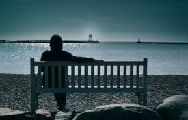 Lady sitting on a bench looking at a lighthouse