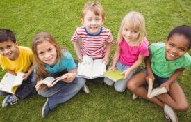 five diverse school-ages children sit outside on the grass holding books.